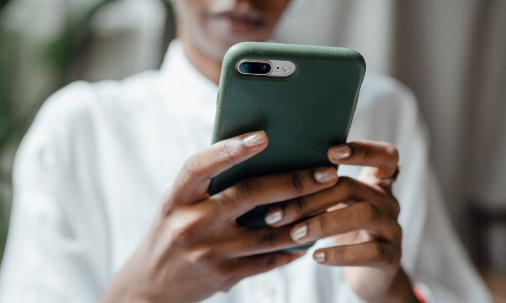 Black woman using iPhone in green case